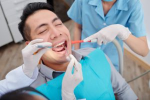dentist-treating-teeth-of-patient-QMBDRY3