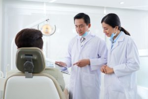 dentists-discussing-information-on-tablet-computer-RYF5M24